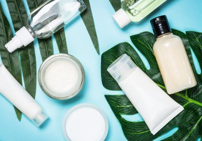 Skin care product, natural cosmetic, cream, tonic, lotion with green leaves. Flat lay image on blue.